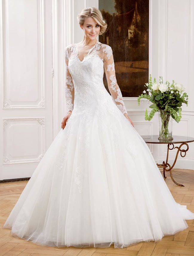 Full tulle skirted wedding dress with lace detailing on the bodice and long sleeves.
