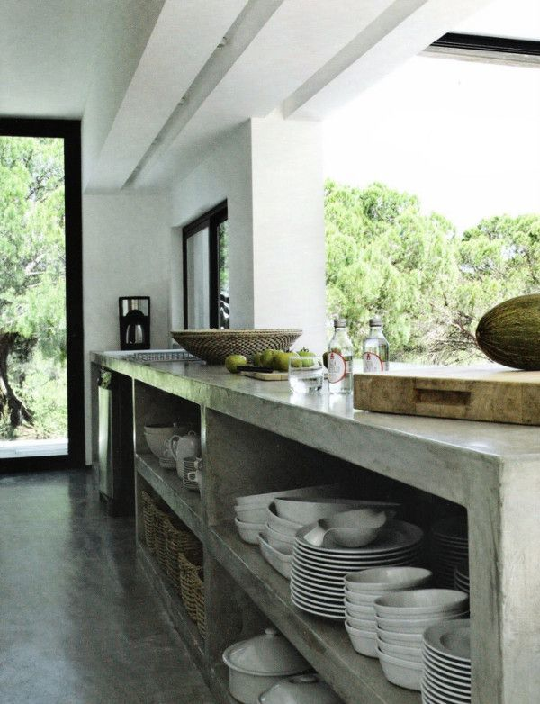 12 Concrete Interiors: The polished concrete kitchen island with open shelving in this photo from French magazine Maison Cote du Sud, provides plenty of storage and workspace, and lends some edge to the somewhat rustic room.