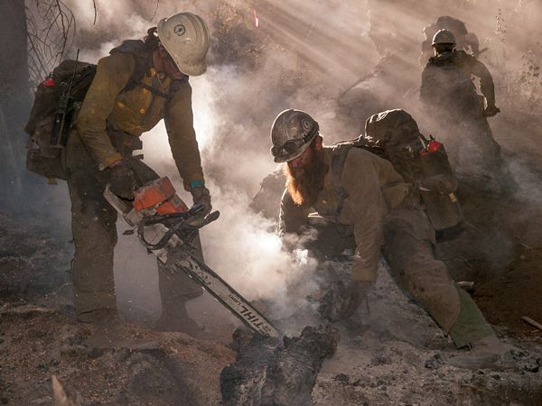 Firefighters in Idaho cut out the hot portion of a log while mopping up the Whiskey Complex fire near the Boise National Forest.