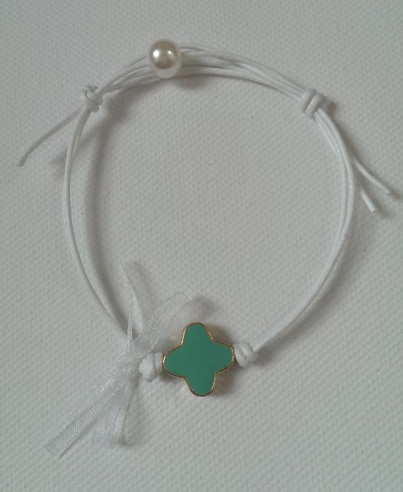 White bracelet with a turquoise enamel cross and pearl.