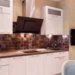 Ручной работой отмечено и кухонное пространство. Плитка на фартуке заглазурована в цвет, который перекликается со шторами у дивана. Она переливается разными оттенками и принимает на себя общий колорит интерьера. Выбранная стилистика позволяет поиграть мягкими тактильными фактурами отделочных поверхностей. Бархатистые стены, оттиски кружева на плитке, натуральные ткани.