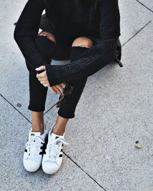Black ripped jeans, black sweater, + Adidas Superstars.
