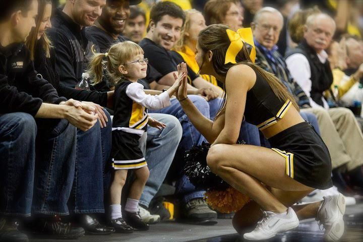 Cheerleader high fives little girl with Down syndrome dressed in a cheer outfit. How sweet!!