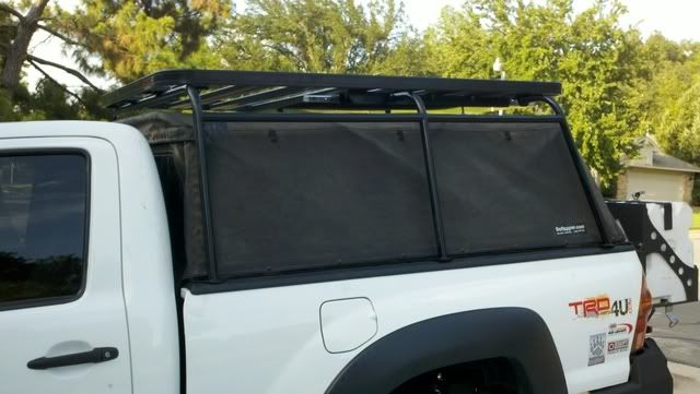 Maybe a roof rack like this one for a full-sized, and a separate roof rack of the same height over the cab. If you know the brand, please leave it in a comment.