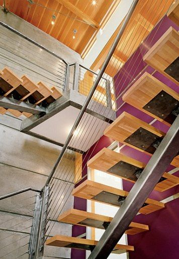 """An open staircase that has """"treads on a single, brushed-steel stringer,"""""""