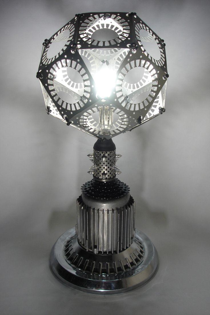 """Lámpara de mesa """"Anthrax""""   Materiales: tapón de carro, foco ahorrador de energía, una carcasa de compresor, filtro de aire, una campana, estrella de bicicleta y 18 láminas de un estator  Medidas: 60cm de alto X 26cm de largo X 26cm de ancho"""