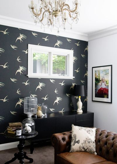Beautiful living room space decorated with a tufted leather couch, black furniture, carpeted floors and one wall covered in swallow wallpaper by Sanderson | Photos by Lisa Atkinson Photographer