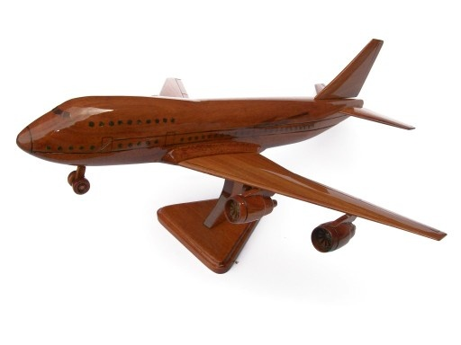 """A beautiful hand carved desktop model of the Boeing 747. The model has been carved from solid mahogany. The model comes boxed and is simple to assemble. The wings, tail fins and stand simply slot into pre-drilled holes on the body of the aircraft. No glue required. Size H 9"""", L 17"""", W 16"""". Visit our website at thewoodenmodelcompany.co.uk to view the full range of our models."""