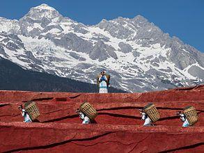 Nakhi emberek kosarakat cipelnek a Jáde Sárkány Havas Hegység Szabadtéri Színpad nyilvános előadásának egy jelenetében. Lijiang, Jünnan tartomány, Kína