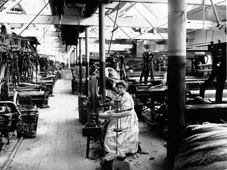 Young girl in the weaving shed at Witney Mill rewinding unravelled power loom bobbins by hand.