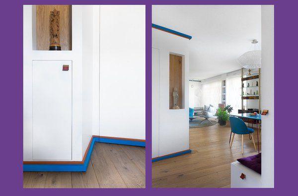 Gros plan sur les poignées en cuir et laiton des rangements de l'entrée qui intègrent désormais une buanderie. Une moulure bicolore, orange et bleu, ceinture la cloison en biais au sol et au plafond.