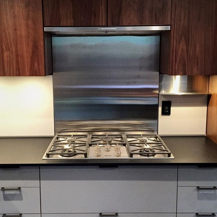 Miele gas cook top with stainless steel backsplash and hood.