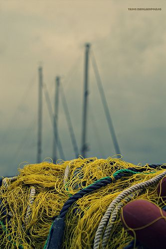 Summer in Trizonia island, Greece.   In my village, Trizonia island, most teenagers occupy with fishing or tourism. Fishing nets are everywhere in Trizonia's harbour.