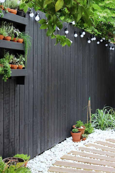 Modern garden with black fencing and white pebbles | Growing Spaces