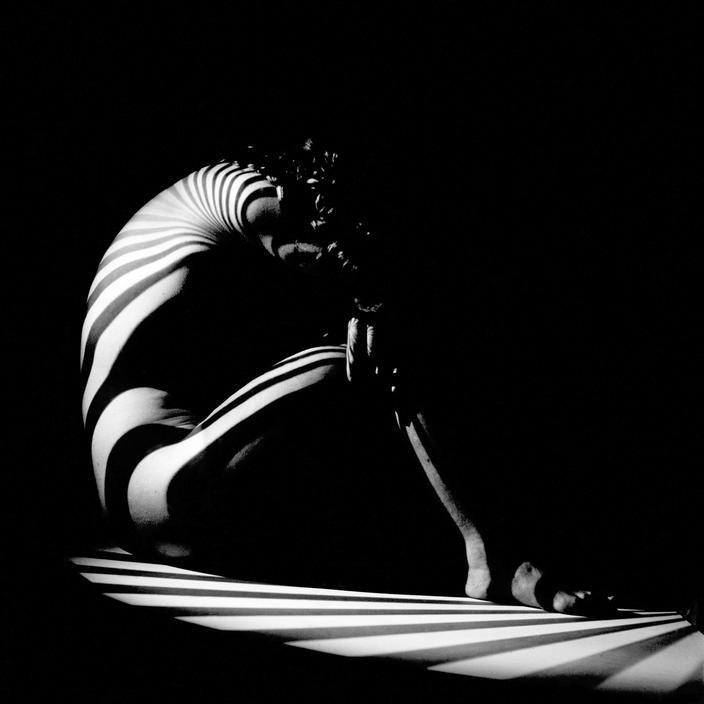 """Werner Bischof  SWITZERLAND. Zurich. """"Zebra woman"""". 1942.  Chiaroscuro  –  Interior  –  Model (artist's)  –  Nudity  –  Stripes  –  White people  –  Zurich"""