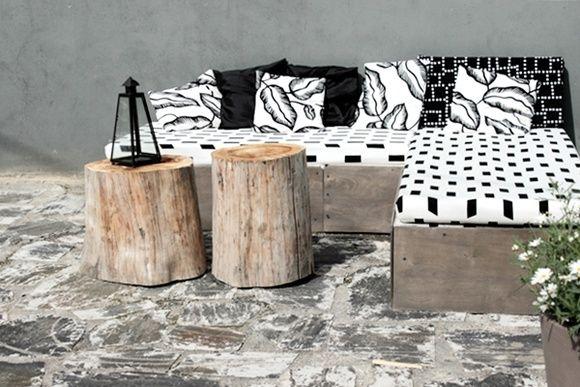 lavasohvassa on muutama lava, vanerit etureunassa ja itse päällystetyt patjat ja tyynynpäälliset. Puupölkyt toimivat pöytinä.