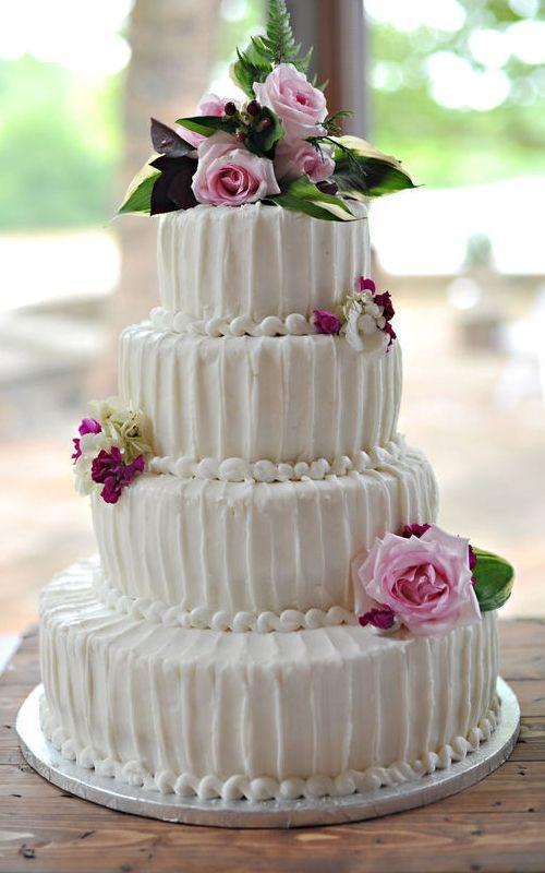 Pastel de boda blanco, redondo a 4 niveles, decorado con flores naturales rosas
