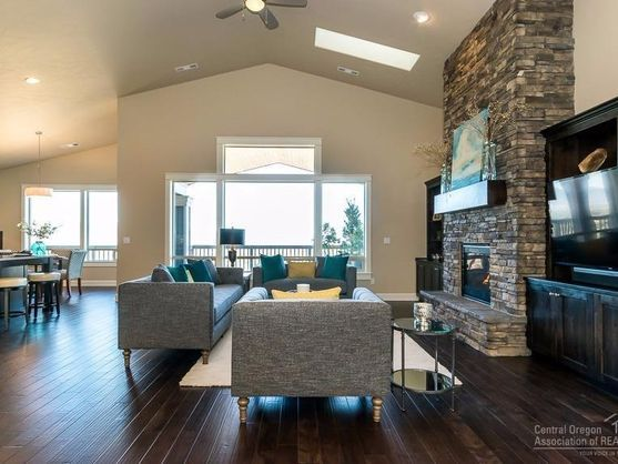 Stunning rock fireplace and hardwood floors ground this airy, open living home in Bend, Oregon