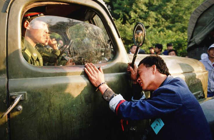 A weary protester pleads with a People's Liberation Army (PLA) officer sitting in his truck to not crack down on the student demonstrators.
