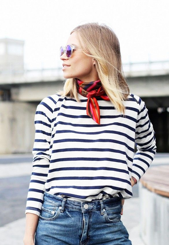 A striped shirt is worn with blue jeans, mirrored sunglasses, and a neckerchief