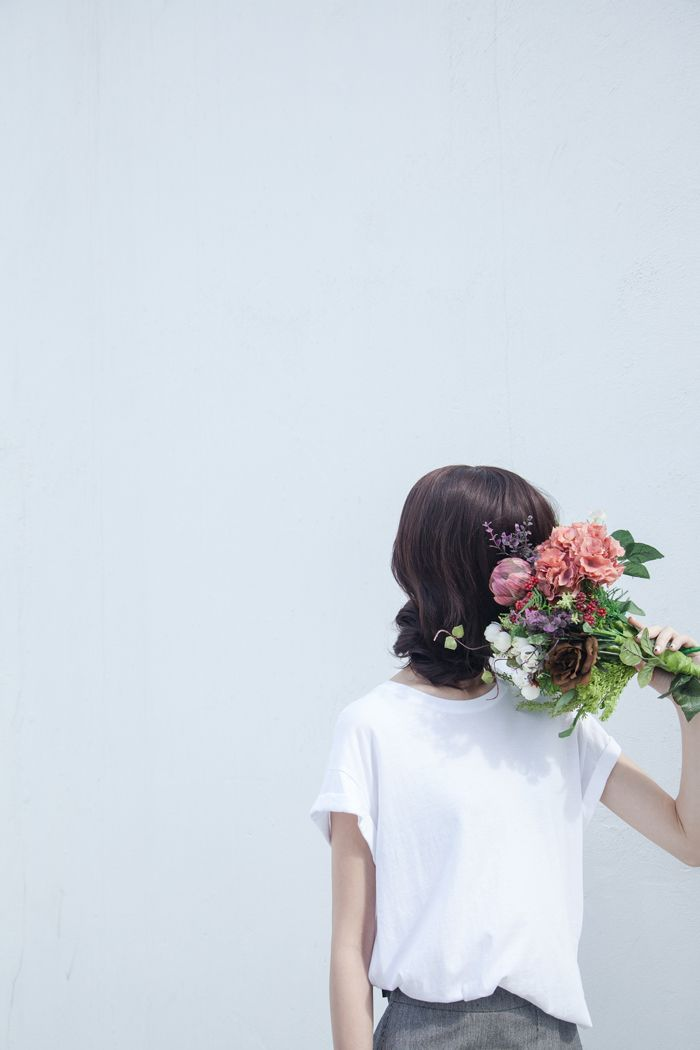girl in white tee shirt holding bouquet of flowers