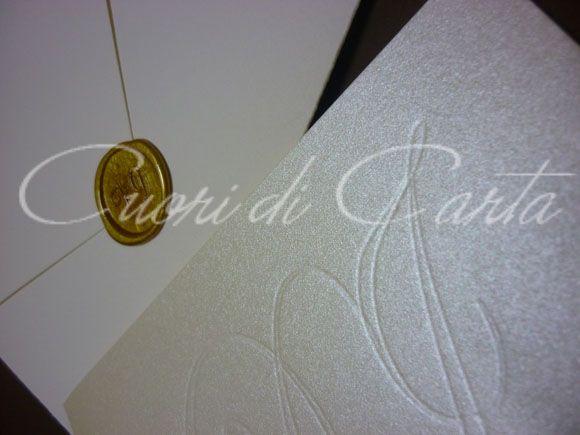 Partecipazione realizzata e scritta a mano, carta perlata e busta in carta martellata, decorata con iniziali sposi incise. Busta chiusa con sigillo in cera lacca con iniziali sposi.