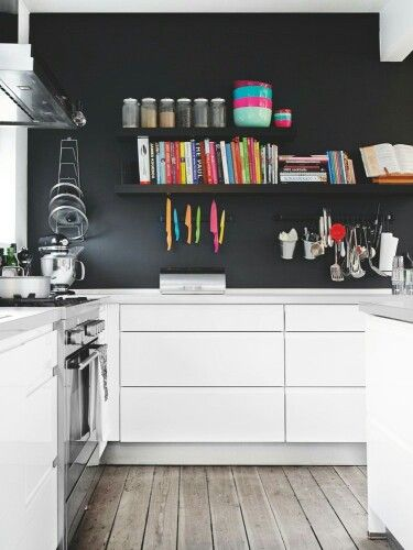 love the black wall with colorful books, etc. above white cabinets and bleached wood floors.