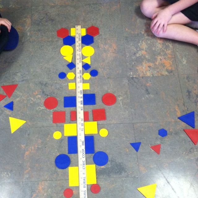 "A meter stick and shape sorting puzzle make a great symmetry activity. Partners use 2 of same shape and take turns placing on either side of ""line"" of symmetry."