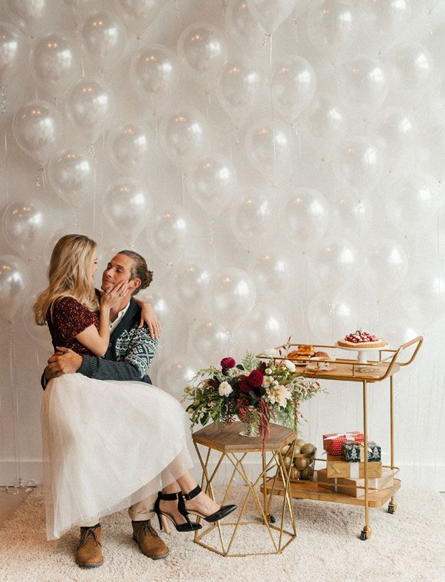 Holiday Engagement Session with a ballon wall and cream, burgundy + gold accents. White tulle skirt