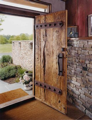 two inch thick oak barn threshing floor and custom hand forged hardware entrance door. Barn siding as interior walls.