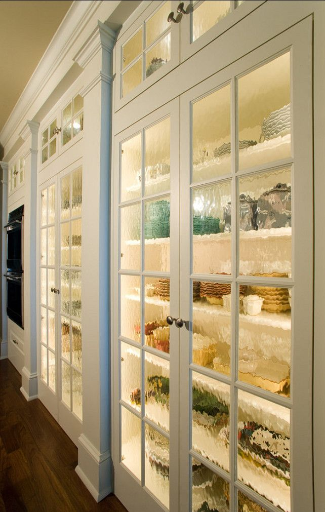 "KITCHEN STORAGE:  ""The custom cabinet doors feature antique glass.  The cabinetry houses unique glassware and dinnerware of the owner, and on the far back portion is the double ovens."""