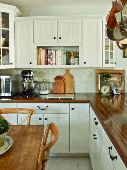 White cottage kitchen, with butcher block countertops and bronze knobs