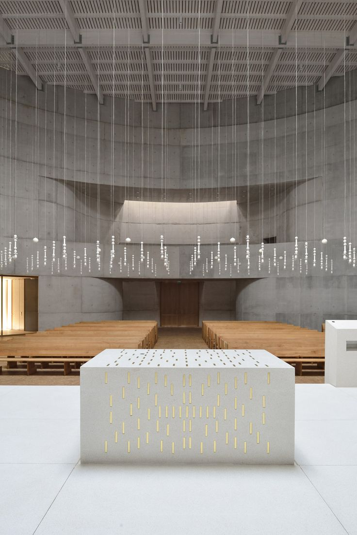 Curved brick chapel featuring 100 handmade clay lamps, which are strung from the ceiling