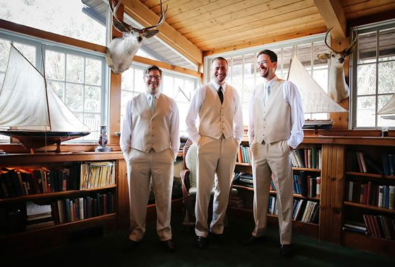 The groom and his groomsmen prepare for the big day in a cedar-lined cabin with mounted deer heads. Wedding Photographer: John and Colette photography & beauty