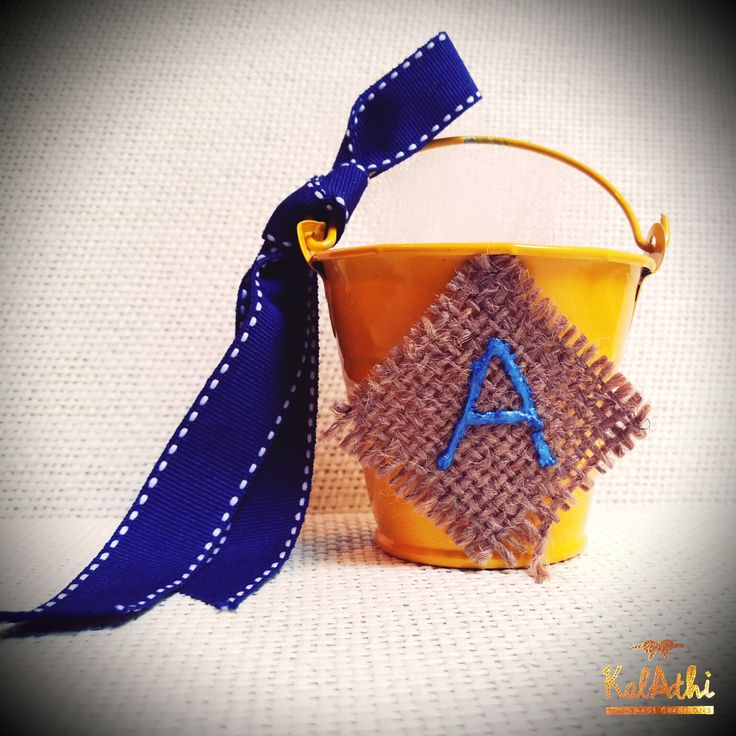 Yellow tin can with navy blue ribbon and initial by KalAthi photo © KalAthi