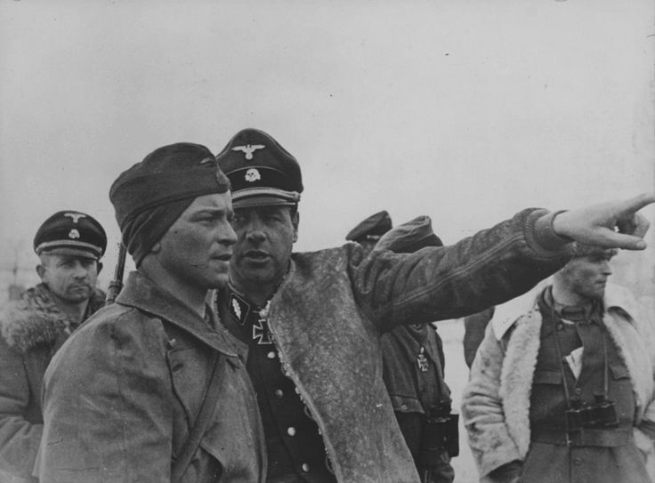 Fritz Witt (center) photographed in March 1943 as a commander of SS-Panzergrenadier Regiment 1 of the Leibstandarte Division. He holds the rank of SS-Standartenführer, but he has abandoned military etiquette and opted for comfort and warmth, commandeering a loose sheepskin jacket. Witt was KIA in Normandy, June 1944.