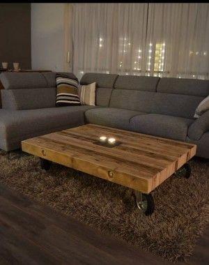 Romantische woonkamer in bruin kleuren met een grijze hoekbank, Houten tafel op wielen en een hoogpolig tapijt.