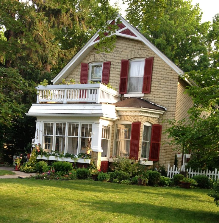 I love the stacked porches and red trim on this old yellow-brick. In the summer, the upper porch is overflowing with flower boxes around the railing.