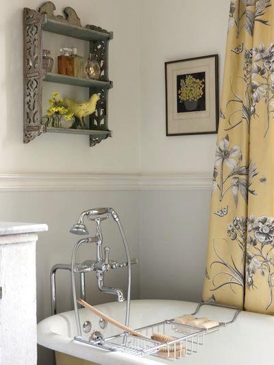 Léger et raffiné. Voici une ravissante salle de bain peinte de jaune paille et de gris pâle, couleurs reprises dans les rideaux, le petit tableau et les accessoires déco de l'étagère suspendue. Le corps de la baignoire a été peint en jaune comme le fond des rideaux tandis que la partie basse du mur a été revêtue de gris perle très pâle. Crédit photographique: HGTV, Conception Sarah Richardson.
