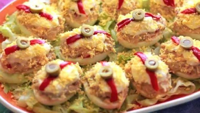 Huevos rellenos de atún: 6 huevos, Salsa rosa, Atún en aceite, Mayonesa, Pimiento rojo asado, Pepinillos, Aceitunas rellenas de anchoa. Cocer huevos y enfriar. Cortar resto ingredientes muy finos y los huevos por la mitad; añadir las yemas (reserva una) y mezclar.Aplastar todo con 1 tenedor y añadir la salsa rosa. Rellenar los huevos. Colócalos sobre una cama de lechuga en un plato. Decorar con mayonesa, yema de huevo rallada, 1 tira de pimiento y 1/2 aceituna. Dejar en nevera hasta servir.