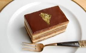 Una din retetele de prajituri festive, celebra prajitura Opera cu blat joconde, strat de ciocolata, crema de cafea, crema ganache si glazura de ciocolata.
