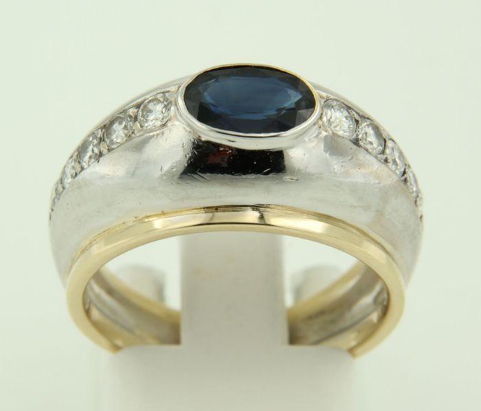 14k bicolor gouden ring bezet met centraal een ovaal geslepen saffier en briljant geslepen diamanten ringmaat 17.75 (55)  ring is circa 12 cm breed en gemaakt van geel en witgoud gewicht 66 gram gezet met 1 x 74 mm x 48 mm ovaal facet geslepen verhitte saffier totaal circa 100 caraat kleur blauwzuiverheid SIEdelstenen zijn vaak behandeld om kleur of helderheid te verbeteren. Dit is niet onderzocht bij dit specifieke object.' - 6 x 27 mm (circa 007 ct ) briljant geslepen diamant totaal circa…