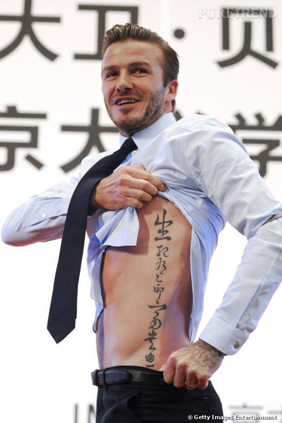 """David Beckham aime les tatouages, ce n'est pas nouveau. Cette année, deux nouveautés : une déclaration d'amour à sa femme tatouée sur sa main et cet impressionnant dicton sur le flanc. """" La vie et la mort sont des rendez-vous pris en avance. Les richesses et les honneurs dépendent du Paradis """". Quel philosophe ce David !"""