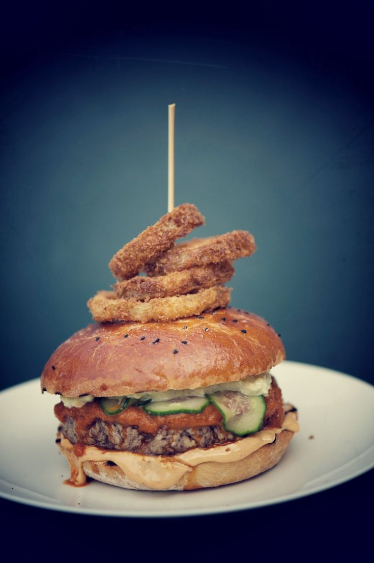 Burger med hjemmelavet brød, ketchup, mayonnaise, remoulade, råmarineret agurkesalat og løgringe