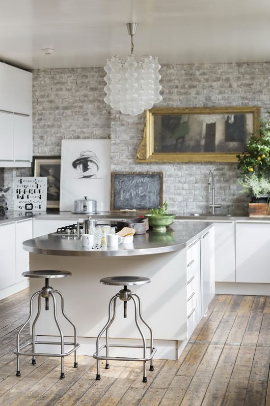 Mix of industrial and elegant kitchen with exposed brick wall, perfect for a kitchen remodel!