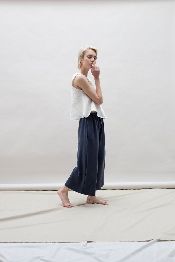 Wide leg crop pants with elastic drawstring waist. Hidden pockets at sides. High rise with a baggy pant leg that hits just above the ankle. A