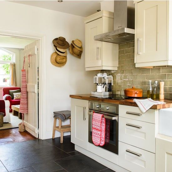 Cream galley kitchen with hat wall display | 19th-century cottage in Devon | House Tour | PHOTO GALLERY | Ideal Home | Housetohome.co.uk