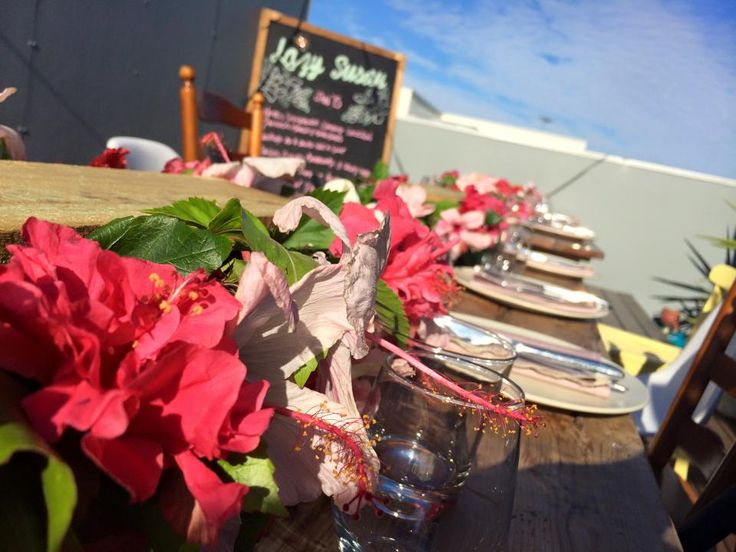 Summer hibiscus hedge tablescape for a tropical rooftop dinner party   Styled by The Inventory for The Lazy Susan Lunch Club, January Rooftop Dinner Party 2015 #hibiscus #tropical #tablescape #pink #festoon #summer #adelaide