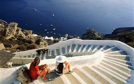 Couple sitting on stairs on mountainside, Santorini
