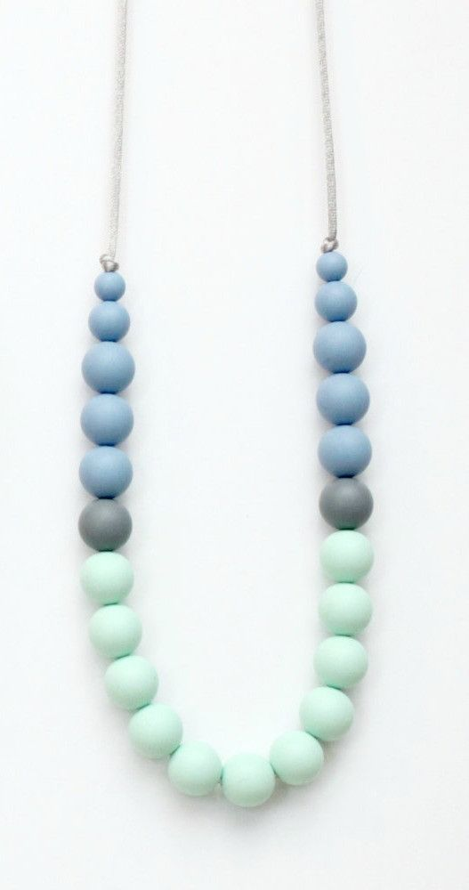 Teething Necklace - Blue/Grey/Mint Measures 31 inches in length Break away clasp Each necklace is made with food grade silicone, silk cord, breakaway clasp and wood beads and rings finished with my or